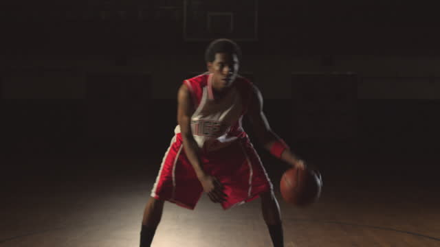 A male basketball player practices passing and dribbling.