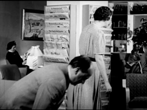 male being handed newspaper inside time life lobby home town newspapers on stack female assistant finding newspaper for male rockefeller center... - bibliothekar stock-videos und b-roll-filmmaterial