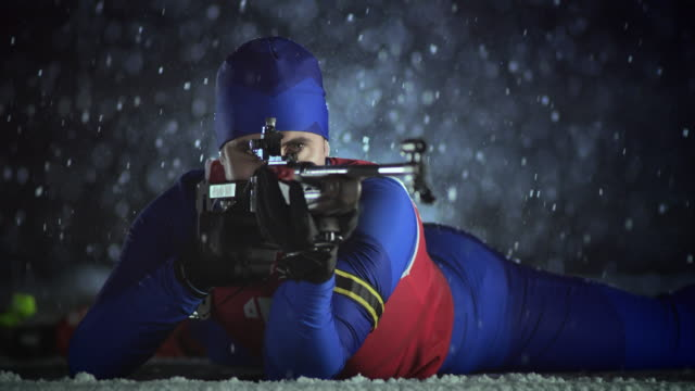 slo mo male biathlon athlete shooting in prone position - biathlon stock videos and b-roll footage