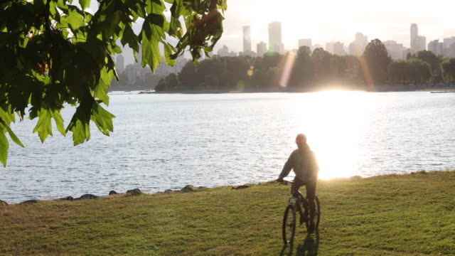 Male bicyclist ascends grass slope above beach, city skyline behind