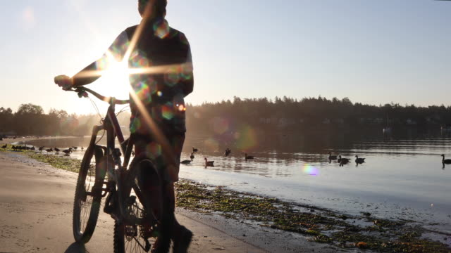 male bicyclist walks along empty beach at sunrise - duck stock videos & royalty-free footage