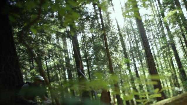 vídeos y material grabado en eventos de stock de ws male biker mountain biking through forest / squamish, british columbia, canada - un solo hombre de mediana edad