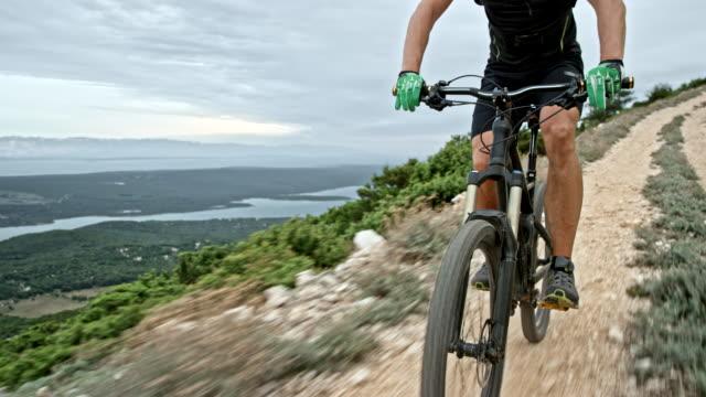 Male biker riding his mountain bike down a mountain ridge