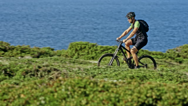 Male biker riding up on top of a hill overlooking the sea in sunshine