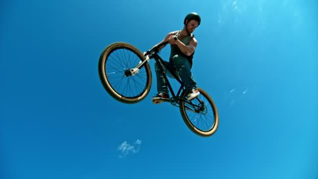 vídeos de stock, filmes e b-roll de slo mo masculino motoqueiro decolando da rampa e fazendo uma curva com a moto de dj no sol - pulando