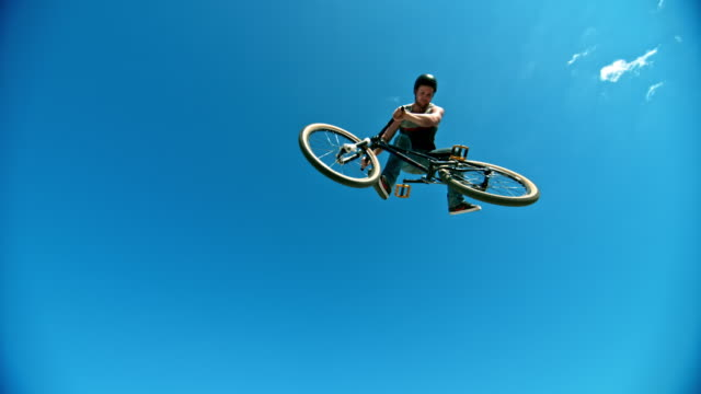 speed ramp male biker taking off the ramp and rotating his bike while airborne in sunshine - jeans stock videos & royalty-free footage