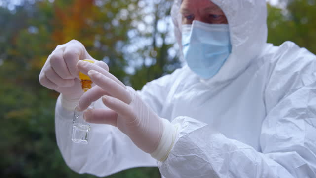 männlicher biologe in schutzkleidung, der einer wasserprobe aus dem fluss ein reagenz hinzufügt - shaking stock-videos und b-roll-filmmaterial