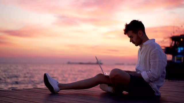 male blogger writing article by the sea - surfing the net stock videos & royalty-free footage