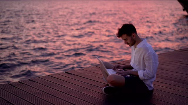 male blogger writing article by the sea - handsome people stock videos & royalty-free footage