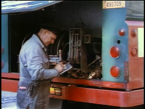 1957 male blue collar worker standing behind truck writing on clipboard - 1957 stock videos & royalty-free footage