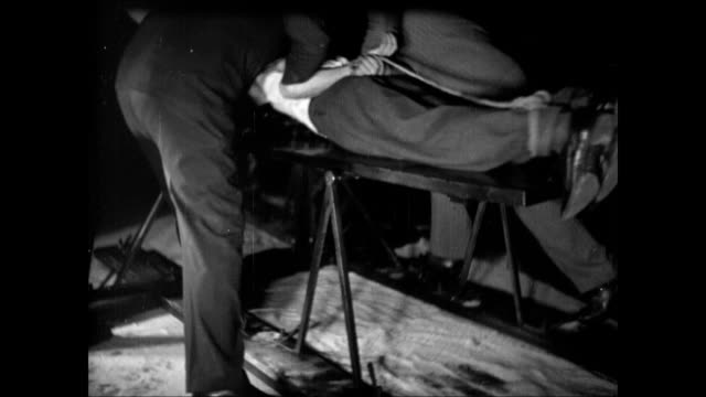 male body w/ hands tied behind back being placed on fallbeil board tu ms blade male hands pulling reclined male head positioning neck in proper place - guillotine stock videos and b-roll footage