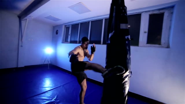 male boxer boxing in punching bag,camera stabilization shoot - mixed martial arts stock videos and b-roll footage