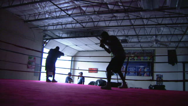 vídeos de stock e filmes b-roll de male boxer in silhouette shadowboxing in warehouse ring, male leaning on corner ring ropes & people standing by open overhead door bg. - lightweight