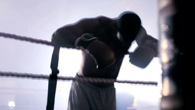 vidéos et rushes de male boxer retreats to the edge of the boxing ring to rest. - s'appuyant