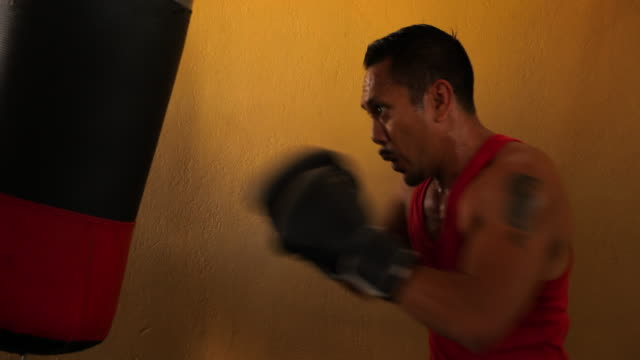 stockvideo's en b-roll-footage met ms male boxer working on heavy bag in gym - stootzak fitnessapparatuur