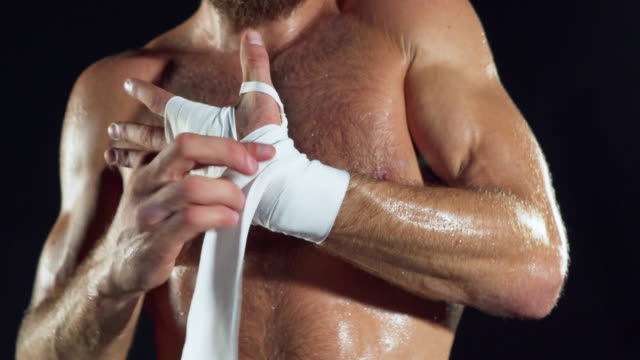 Male boxer wraps his hands with white handwrap before the fight training.Boxer wrapping hands.