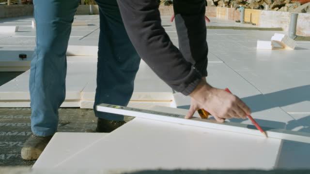 vidéos et rushes de générateur de ds mâle mesure élargi polystyrène expansé pour isolation des fondations - ouvrier