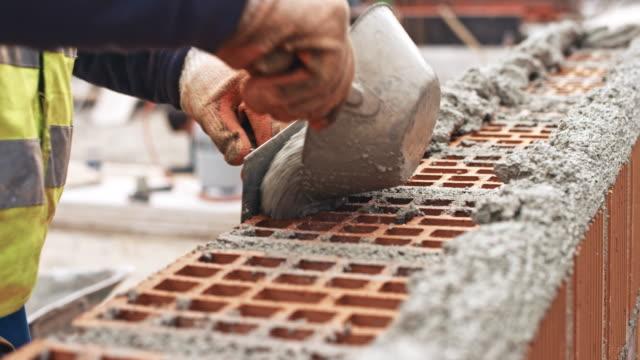 männliche baumeister platzieren auf die ziegel beton - beton stock-videos und b-roll-filmmaterial