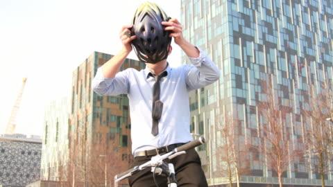 vidéos et rushes de homme d'affaires en vélo à l'extérieur du bureau exécutif - casque