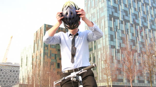 male business executive on bicycle outside office - helmet stock videos & royalty-free footage