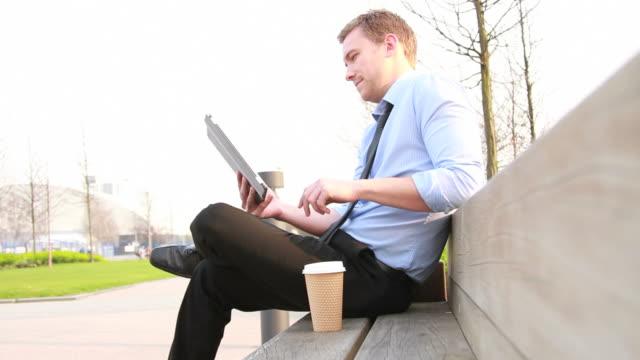 vídeos de stock e filmes b-roll de executivo de negócios masculino sentado fora no parque - banco de parque