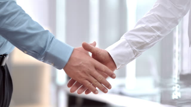 slo mo pan male business handshake - colleague stock videos & royalty-free footage