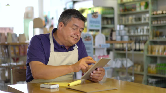 Male business owner of a food market doing the books using a tablet and taking notes on a notepad
