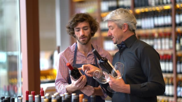 Male business owner of a winery teaching his sales clerk differences about two wine bottles