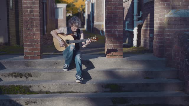 male busker playing acoustic guitar, sitting on some stone steps outside a building on august 8, 2020 in bristol, uk. - hobbies stock videos & royalty-free footage