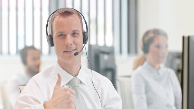 slo mo ds male call center operator giving thumb up - customer service representative stock videos & royalty-free footage