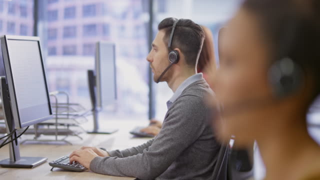 r/f male call centre agent working at his station - headset stock videos & royalty-free footage