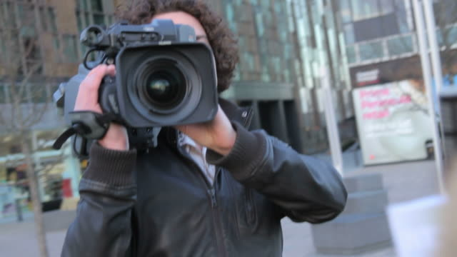 male camera opperator and female presenter on location broadcasting - journalist stock videos & royalty-free footage