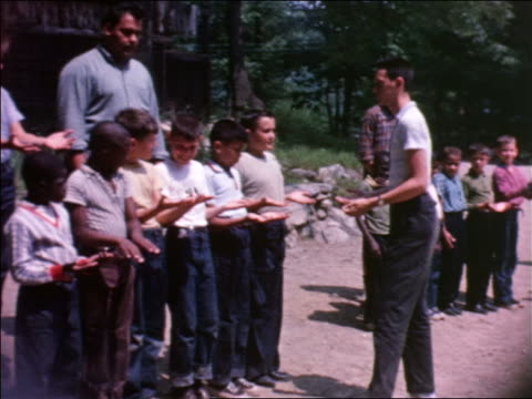 1964 pan male camp counselor inspecting hands of line of boys outdoors / home movie - summer camp helper stock videos & royalty-free footage