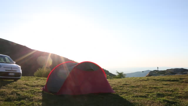 male camper returns to tent at sunrise - stationary stock videos & royalty-free footage