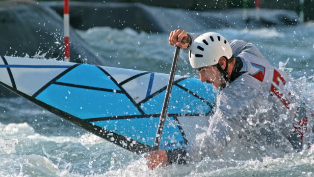 SLO MO Male canoe slalom competitor paddling  in competition