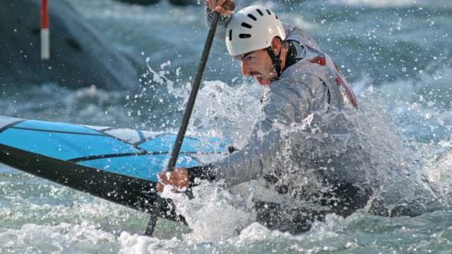 slo mo male canoe slalom competitor paddling through the gates - the competition stock videos and b-roll footage