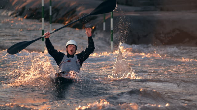 SLO MO Male canoeist celebrating his win by raising his hands at finish