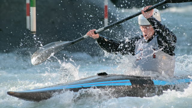 SLO MO Male canoeist striking through water on canoe slalom course