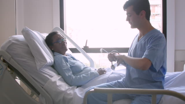 vídeos de stock e filmes b-roll de male cardiologist talking to his patient while she is lying down on hospital bed and then using his stethoscope - profissional de enfermagem