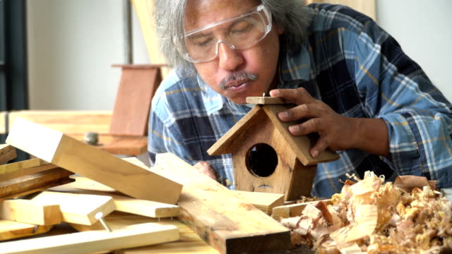 male carpenter blowinng wood out after sanding a bird house in the workshop - birdhouse stock videos & royalty-free footage