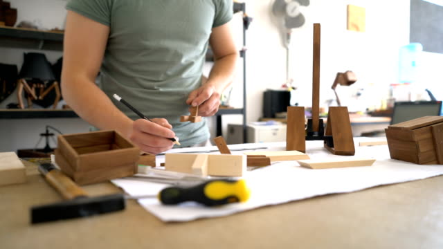 male carpenter drawing and measuring in his workshop. creative focus and cropped footage. - calliper stock videos & royalty-free footage