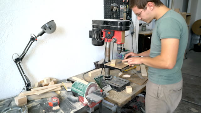 Mâle charpentier des pièces en bois dans son atelier de perçage