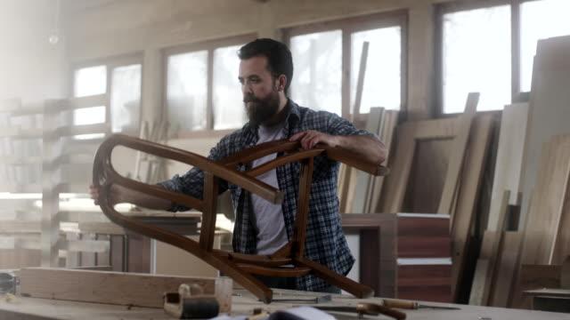 male carpenter in furniture workshop assembling chair - artigiano video stock e b–roll