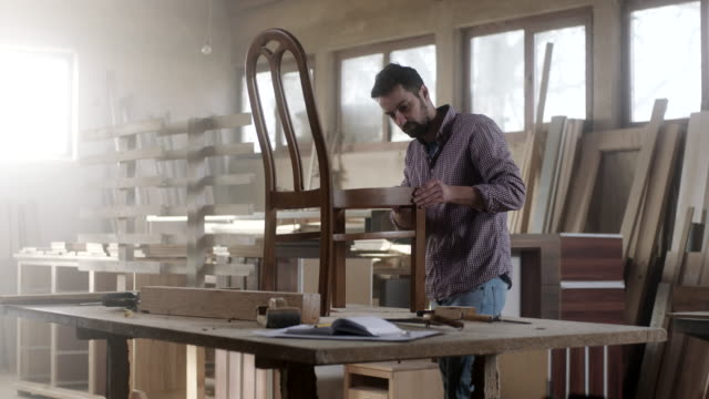 vídeos de stock e filmes b-roll de male carpenter in furniture workshop assembling chair - design