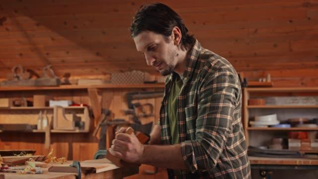vídeos de stock e filmes b-roll de male carpenter using a jack plane to shape a plank in his workshop - camisa com botões