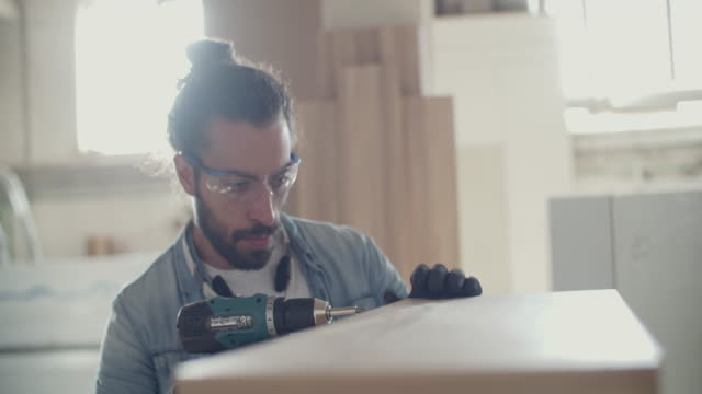 male carpenter using electric screwdriver in his workshop - repairing stock videos and b-roll footage