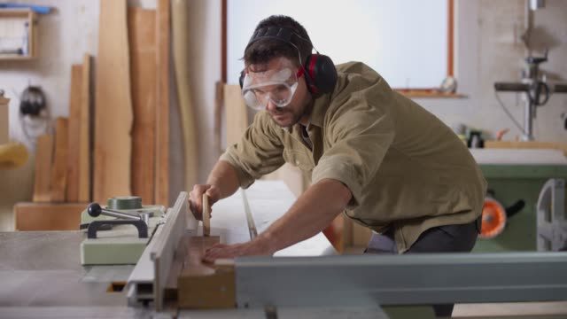 ds male carpenter wearing eye and ear protection while cutting planks on the table saw in her workshop - plank stock videos & royalty-free footage