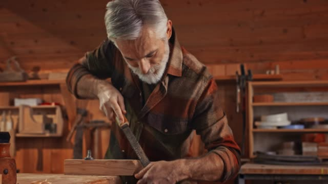 male carpenter with a grey beard and hair using a file to finish a part of workpiece in his workshop - carpentry stock videos & royalty-free footage