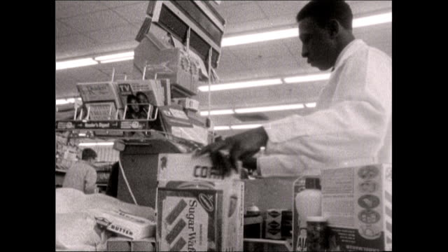 male cashier rings up a customer's purchases - bbc archive stock-videos und b-roll-filmmaterial