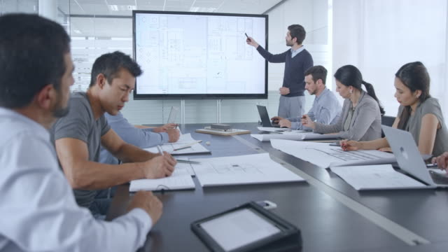Male Caucasian architect presenting plan details on the large screen in the conference room